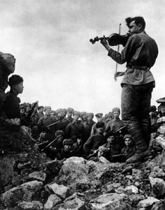 A Russian soldier playing violin in a ruined building for his fellow soldiers. Photographed in 1943 by Yakov Khalip.