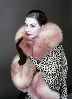 Vogue, 1954. Model wears black gloves with a leopard (or ocelot?) fur coat with fox collar and cuffs.