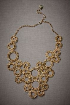 Drip-Drop Necklace  $280.00     Like rain falling on a golden pond, hand crocheted and beaded circles form a mesmerizing rhythm in their rippling repetition