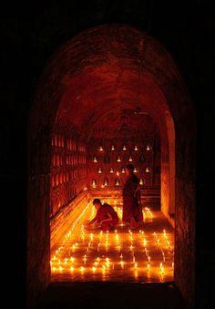 Monks lighting Prayer Lamps