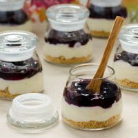 A recipe for mini blueberry cream cheese pies in small jars. The pies have a graham cracker crust, cream cheese filling, and blueberry topping.