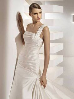 """Pronovias Grecia NECKLINE: One shoulder SILHOUETTE: Fit n' Flare FABRIC: Silk Duponi FEATURES: Silk Duponi gown gathered asymmetrically at the hip. Covered buttons over a zip closure. TRAIN: Chapel CONDITION: Once loved and worn Size: 2, hemmed to 5'5"""" PRICE: $1800.00"""