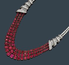 BURMA RUBY AND DIAMOND NECKLACE, ca. 1945. Platinum and yellow gold 750. Very fancy necklace of a double Rivière of brilliant-cut unheated oval Burma rubies weighing ca. 65.00 ct. Total weight of the baguette-cut diamonds ca. 6.50 ct and total weight of the brilliant-cut diamonds ca. 9.00 ct. - by Koller Auctions