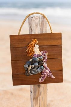 Everyone needs a magical mermaid! This beautiful piece hand crafted from shells and shell pieces collected on the OBX! Each piece is unique. 10x10 size and ready to hang anywhere in your home or beach cottage!