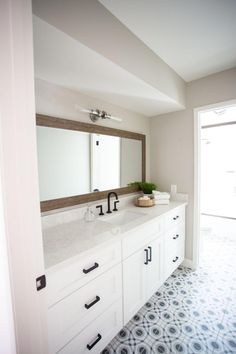 A long wood-framed mirror runs parallel to the marble vanity countertop with backsplash lip. Black cabinet handles on the white vanity compliment the black and white pattern on the floor tile decorating the otherwise understated design.