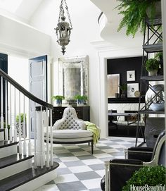 """""""I'm a traditionalist at heart, and this is my David Adler foyer,"""" says Windsor Smith, who chose statuary marble and Bateig Blue limestone for the floor of her Los Angeles house. The Entry Round Settee, from Windsor Smith Home, is upholstered in a Rogers & Goffigon silk. An old Venetian lantern and a new Venetian mirror add a glint of silver. The paint on the walls is Benjamin Moore's Titanium.   - HouseBeautiful.com"""