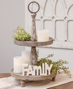 """The Weathered Two-Tiered Tray is a farmhouse inspired accessory perfect for kitchens, living rooms, or dining rooms. This wooden two-tiered tray is a freestanding tabletop accessory with three wooden legs, two wooden trays, two distressed wooden beams for support, and a metal circular loop on top. It measures 21"""" high and 12"""" in diameter and is perfect for decorating with framed signs, candles, florals, or sitters. The trays can also be used as a functional accent to store knick-knacks… Kitchen Tray, Kitchen Island Decor, How To Decorate Kitchen Island, Dining Room Table Centerpieces, Table Top Decorations, Kitchen Decorations, Dining Decor, Centrepieces, Countertop Decor"""