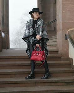 Schwarzes Outfit mit Karo-Cape und roter Tasche - erwachsener Rocker-Chic.