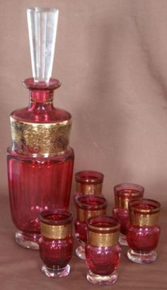 Signed Moser Cordial Decanter Set; Cranberry and clear cut glass w/ gold borders. Decanter is 12 High.