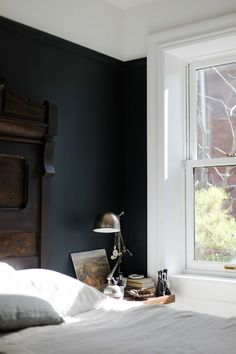 The calmness in this bedroom - the dark paint, the headboard, the light, that window