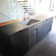 A Blackened Stainless Steel clad countertop and cabinet faces and cantilevered steel stairs by Architectural Elements.  ArchEle.com