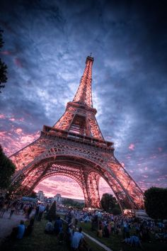 The eiffel tower under a striking and vibrant blue and pink sky.