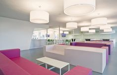 Office Interior Designs with Color Block Theme : Pink Sofas White Sofas White Round Chandeliers White Wall Grey Floor