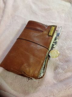Re Purposed a old leather bag into a Travel Midori notebook. Made a pen holder with duck tape