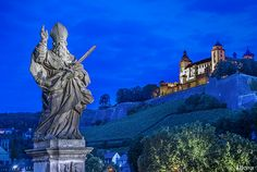Illuminated statue on the Alte Mainbruecke bridge with illuminated castle, Feste Marienberg, in the background, night shot, Wuerzburg, Bavaria, Germany