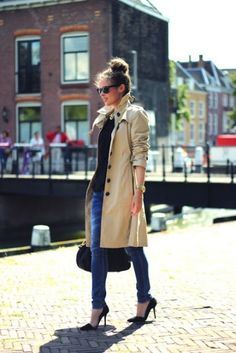 """trench coat topped over a basic black sweater and jeans, pumps and a chic bun"""
