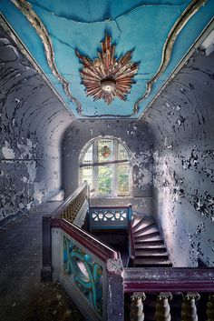 Window has beautiful stain glass abandon mansion still has class. Look at the wood work on the stairs.
