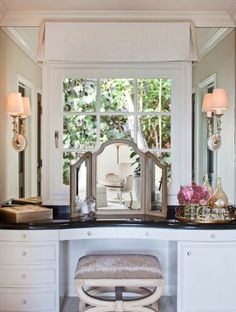 Dressing room boasts curved, built-in vanity topped with black countertop and folding vanity mirror paired with crushed velvet stool situated under window dressed in pleated valance flanked by sconces mounted on mirrors.