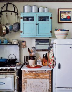 Vintage kitchen. I love the weathered cabinet below and the splash of color the turquoise cabinet above.