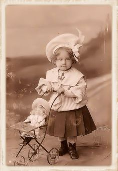 "Antique photo of little girl wearing an adorable outfit (love the hat!) with her lovely little ""stroller"" and her doll who is also wearing a large ht (that doll would be worth a fortune nowadays)."
