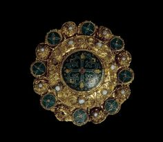 Disc brooch: gold; enamelled; central domed disc decorated with floriate cross: quatrefoil at crossing; surrounding band of filigreed bosses alternating with roundels with enamelled crosses; coloured enamel: translucent emerald green; opaque dark blue; opaque dull yellow and red; set with small pearls in collets.      Ottonian or     Byzantine  - circa 975-1025.