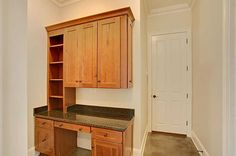 Office desk right off of the kitchen, complete with wooden cabinetry and granite countertop.