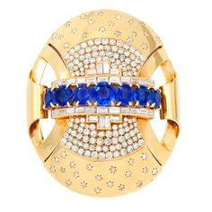 1940s Monumental Gold and Jeweled Clip. Large 18K gold, sapphire and diamond oval clip in the style of Van Cleef & Arpels with approximately 12 cts of sapphires and approximately 7 cts of diamonds.