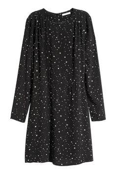Een jurk van geweven, licht onregelmatige kwaliteit met een geprint dessin. De jurk heeft lange mouwen, platte plooien bij de schouders, een naad in de tail