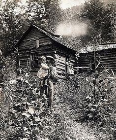 A mountaineer's home in the Blue Ridge Mountains in the Appalachian Mountains. The mountaineer is holding a child while he stands in his front yard planted with vegetables.