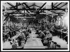 Convalescent British soldiers in France having a rest in a recreation room in a hut provided for them by the B.R.C.S. | Many are reading and writing letters