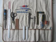 "A knife for slitting folded paper; 12"" metal ruler without a cork back; Carpet Scissors; self-made sand paper board made from book board and sandpaper; various bone folders; scalpel #3 holder, #11 blade (from medical supply store); awls for punching holes/marking measurements; micro spatula for spreading glue in tight spaces; Dividers; metal angle for accurate squaring; utility knife; white eraser; HB & 3H drafting pencils."