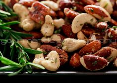 Fragrant fresh rosemary springs are finely chopped, a pinch of cayenne pepper and red pepper flakes are added for a bit of heat and some olive oil coats an assortment of mixed nuts that go into the oven to toast and bring out their rich flavor.