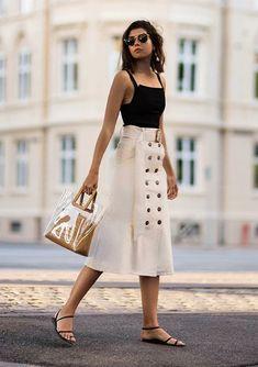 Como usar alfaiataria no look casual. Regata preta, saia midi bege, rasteirinha de tiras, bolsa de plástico