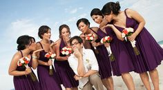 Bridesmaids blow a kiss to the groom on the beach! In purple, convertible knee length bridesmaid dresses. | Palace Resorts Weddings ®