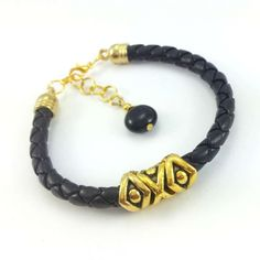 Bransoletka wykonana z rzemienia ze skóry ekologicznej w kolorze czarnym ze złotymi koralikami z mosiądzu.