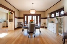 Transitional Dining Room Features Oak Flooring & White Cabinetry