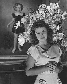 Here's a 1940s photo of actress Shirley Temple with her childhood portrait in the background.