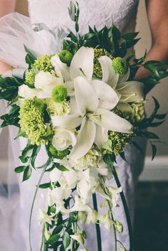 Cascading Bridal Bouquet of White Oriental Lilies, Roses, and Dendrobium Orchids, with Green Hydrangea and Button Mums, and White Tulle.