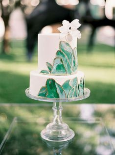 Two tier white cake with marbled green leaves edged in gold