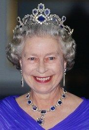 Purchased by King George VI from Carrington & Co and given to Princess Elizabeth as a wedding present in 1947. The necklace originally consisted of eighteen emerald-cut sapphires in diamond clusters. In 1952 it was shortened by four stones, the largest of which was converted into a pendant to the necklace in 1959. The pendant now also has a pin fitting for wearing as a brooch. A tiara and bracelet was made to go with the suite.