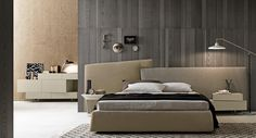 Wing_system_tall bed with Twice headboard upholstered with Opis and Billionaire fabrics. The headboard fixed to the wall and the bed-frame, which is conical on 4 sides, is independent so that it can be positioned in total freedom. By Presotto
