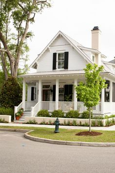 The small cottage plans featured here showcase a charming Southern cottage farmhouse with white clapboard siding, black shuttered windows, and a quintessential front porch that wraps around the side!