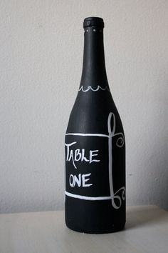 """Chalk Week"" (Day 4) For all the wine lovers out there and anybody who diggs the DIY vibe... Black wine bottles make an excellent canvas for chalk art. Add a single flower that works with the color palate of your celebration and you've got a stylish centerpiece. -mp :)"