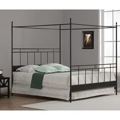 The antique black finish and clean lines of this king-size metal canopy bed create an attractive and airy focal point for your bedroom decor. Depending on personal preference, drape fabric from the top rods or leave the frame unadorned.