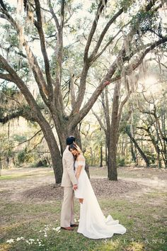 Sun flare picture of bride and groom in oak trees