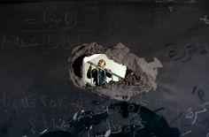 A Palestinian schoolgirl is seen through a hole in a blackboard days after an Israeli strike hit a school in Gaza City. Israel launched an offensive on Nov. 14 in a bid to halt months of Palestinian rocket attacks. Gaza Strip, November, Nov 21, Schoolgirl, Israel, Product Launch, Rockets, City, Wednesday