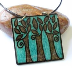 Art Jewelry, Skillfully Wood Burned and Hand Painted.    Square Tree Wood Burned Pendant:    This pendant is made with wood that has been etched with a wood burner and hand painted. It is then coated with resin for a high-gloss, protective seal. This pattern will not fade or rub off in any way, as it is burnt into the wood.    It comes on a brown waxed cotton cord that adjusts in length between 16 and 19.    Please see ruler photograph for pendant dimensions.    View other items in my Burnt…
