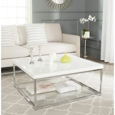 Give your family room a modern update with this lacquered coffee table. The contemporary coffee table features a white and chrome finish that complements any color scheme. A shelf is built into the bo