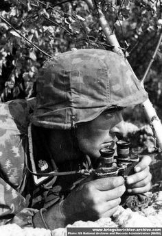 Close up of Waffen SS grenadier with Zeiss standard issue field glasses somewhere on the Eastern Front. Note the full camouflage helmet cover and camouflage smock. The Waffen SS required all battle line troops to wear full camouflage kit.