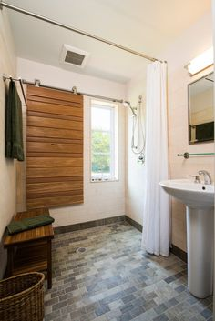 Privacy. The shutter here allows the bathroom to benefit from natural light while preserving privacy when needed. In a wet environment, like this shower, the shutter should be constructed of a durable, rot-resistant hardwood and the track should be stainless steel.